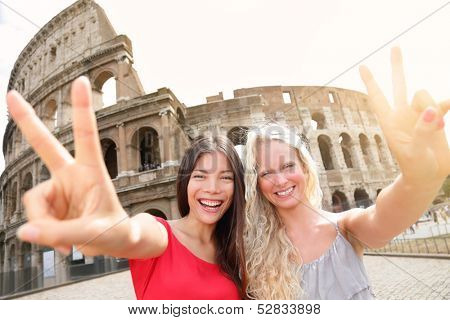 Travel tourist girl friends by Colosseum, Rome. Happy girlfriends tourists showing victory hand sign gesture in front of Coliseum. Beautiful young happy blonde girl and multiracial Asian woman, Italy.
