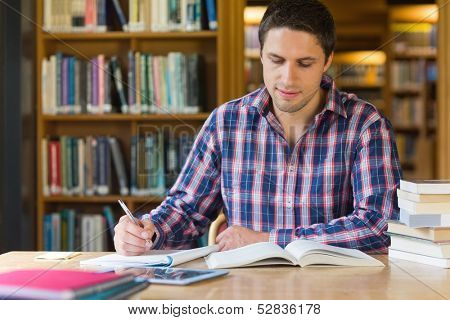 Concentrated mature male student writing notes at desk in the library