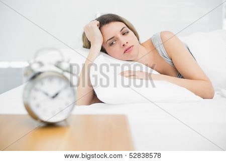 Tired brunette woman lying on her bed gazing at home