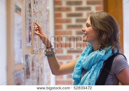 Cheerful student pointing at notice board in school
