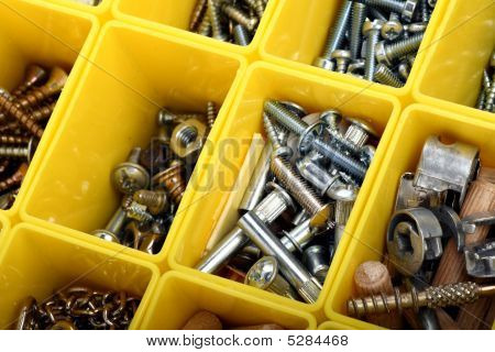 Screws, Bolts, Nuts And Other Carpenter Stuff In A Yellow Plastic Toolbox