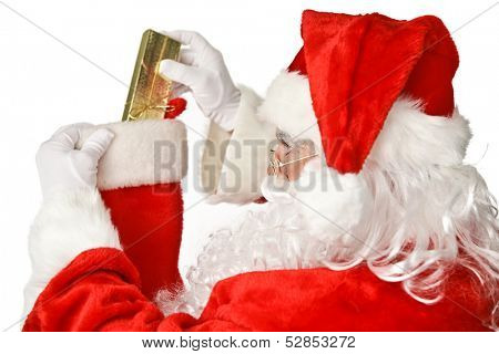 Santa Clause putting a shiny Christmas present into a stocking.  Isolated on white.