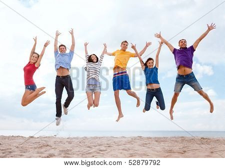 summer, holidays, vacation, happy people concept - group of friends jumping on the beach