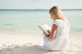 Blond Woman On Beach With A Book