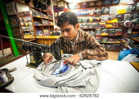 KATHMANDU, NEPAL - DEC 20, 2013: Unidentified Nepali man does embroidery on clothes in a small workshop. Nepal is one of poorest and least developed countries of the world, unemployment rate of 46 %.