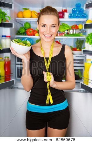 Healthy cheerful girl holding in hand bowl with fresh tasty green salad, dietitian recommending eating vegetables, healthy organic nutrition concept