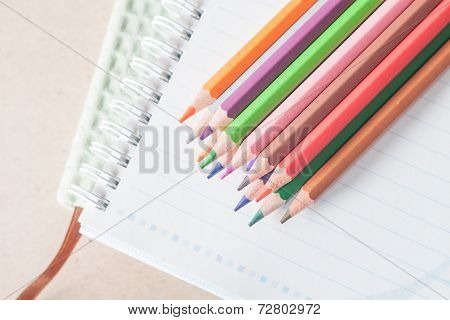 Top View Of Colorful Pencil Crayons On Spiral Notebook And Green Notebook