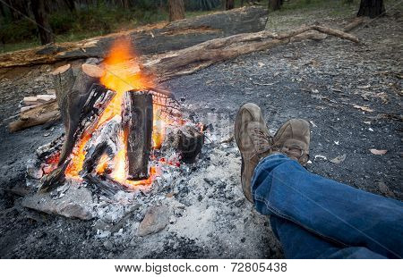 Person warms their feet next to a campfire at dusk camping in the woods poster