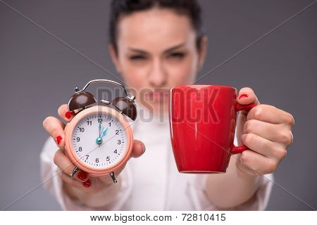 Close-up portrait of beautiful happy girl holding an alarm clock