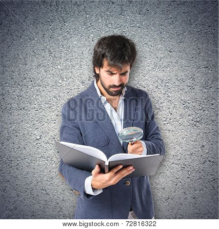 Businessman With Loupe Reding A Book Over Textured Background