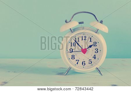 Retro Vintage Style Classic White Alarm Clock On Vintage Blue Background For Daylight Saving Or Time