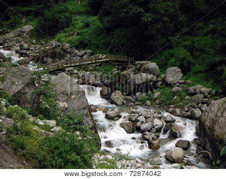 Makeshift Wooden Bridge Crossing A Mountain River
