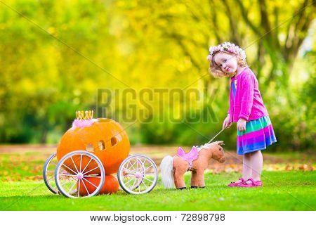 Cute curly little girl playing Cinderella fairy tale holding a magic wand next to a pumpkin carriage having fun in an autumn park at Halloween poster