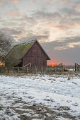 Animal shelter at sunrise seen from the side of a gravel and snow covered road. poster