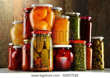 Jars with pickled vegetables fruity compotes and jams in cellar. Preserved food poster