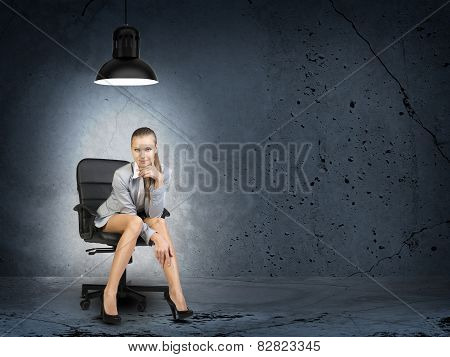 Businesswoman sitting in poorly lighted room