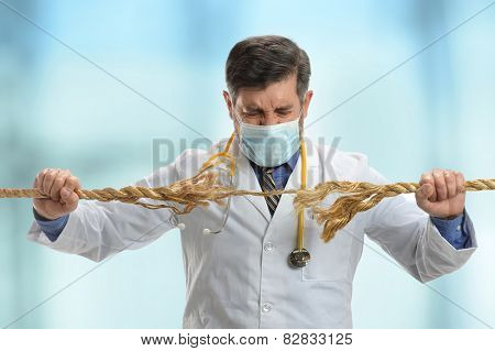 Doctor holding frayed rope inside hospital building