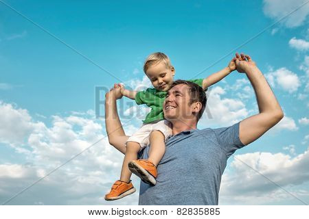 Son seating on the father under beautiful sky with sun