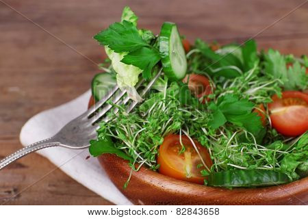 Cress salad with sliced cucumber, cherry tomatoes and parsley in glass bowl on rustic wooden table background