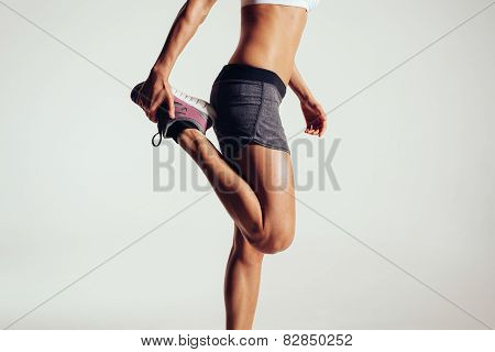 Cropped image of a fitness woman stretching her legs against grey background. Fit female runner doing stretches. poster