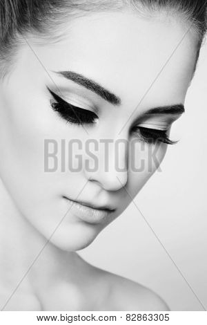 Close-up black and white portrait of young beautiful girl with cat eye make-up