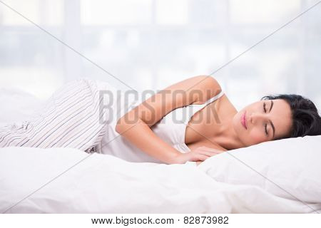 Young woman sleeping in striped pyjamas