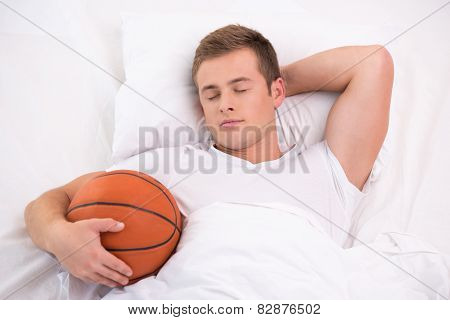 Young man sleeping in bed with basketball