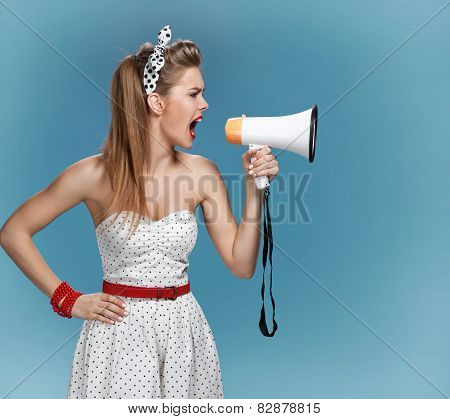 Nervous pin-up girl screaming with megaphone, mouthpiece, speaking trumpet