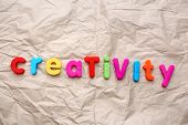 Creativity motto by alphabet letters on crumpled paper background poster