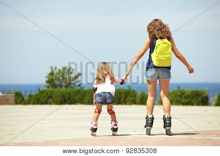 Young mother with her 5 years old daughter rollerskating in park, rear view