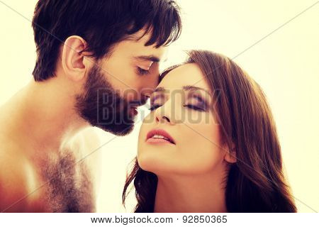 Handsome shirtless man fondly whispering to woman's ear. poster