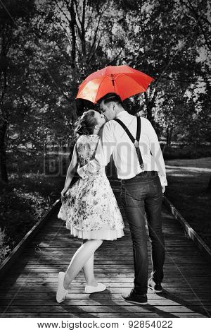 Young romantic couple in love flirting in rain, man holding red umbrella. Dating, romance, black and white