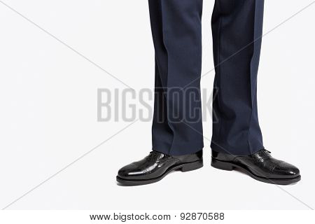 Man In Stylish Black Shiny Male Semi-brogue Posing In Direct Position Against White.