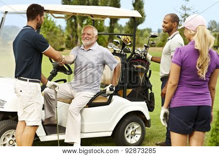 Golf partners greeting on the fairway around golf cart.