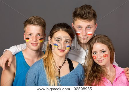 Four teenagers with flags drawn on the faces
