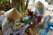 BEN TRE VIET NAM- JUNE 2: Asian worker working at wood workshop Vietnamese people make product from coconut tree trunk tradition craft in polluted enviroment Mekong Delta Vietnam June 2 2015 poster
