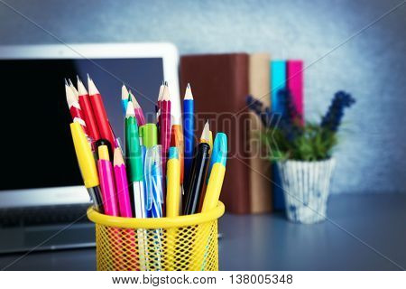 Pencils and pens in metal holder with laptop close up
