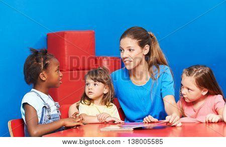 Children talking during language promotion in kindergarten with speech therapist