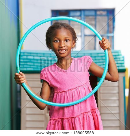Happy african girl playing with hula hoop in kindergarten