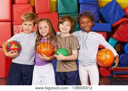 Happy children as team with different balls in a gym of a preschool