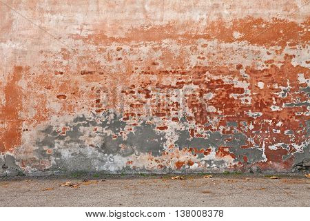 old wall with peeling paint and scratched stained plaster - grunge background of urban decay