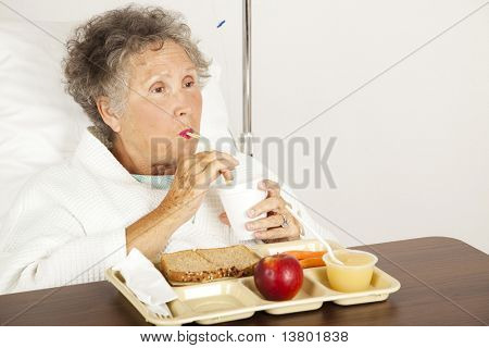 Senior woman in the hospital, eating lunch and drinking from a straw.