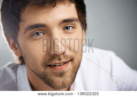 Close up portrait of smiling elegant handsome young businessman in white shirt looking at camera. Studio, isolated on grey background.