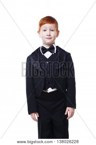 Little cute redhead boy in tailcoat tuxedo pose standing still. Portrait of well-dressed child in bow tie isolated on white background