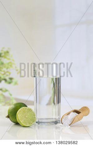 A glass of water, lemon, soda bicarbonate