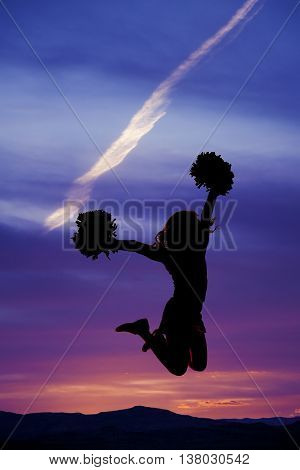 A silhouette of a cheerleader jumping into the air with her pom poms.