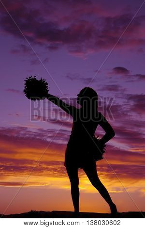 a silhouette of a woman in her cheerleader with a pom pom.