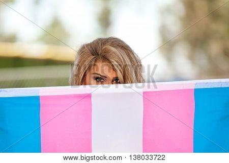 Transgender hiding part of her face behind Transgender Pride flag.