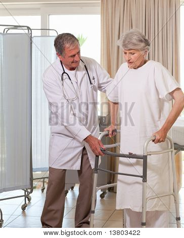 Senior doctor helping his patient to walk