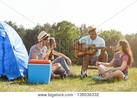 Happy young friends are singing to a guitar in nature. They are sitting near tent and smiling. Man is playing music with inspiration